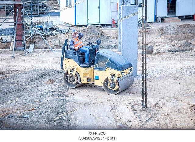 Young male labourer taking a break on steamroller at construction site