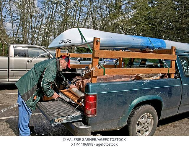 This middle aged Caucasian man is preparing the back of his truck with camping gear with a kayak loaded on top in readiness for a camping trip