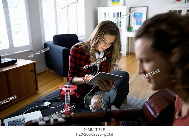 Couple with guitar and ukulele using digital tablet
