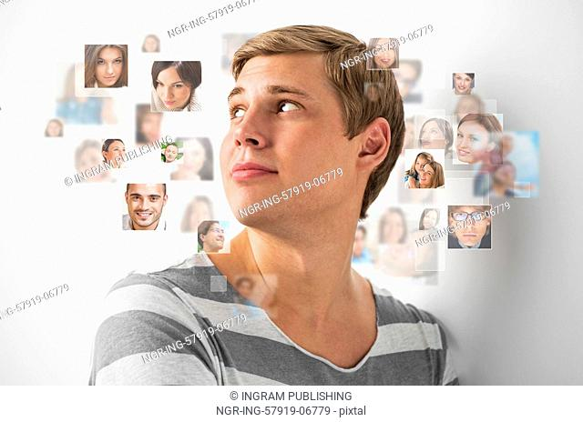 Young man standing and smiling with many different people's faces around him. Technology social media network of friends and communication