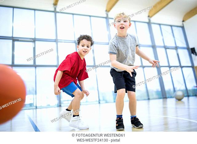 Two schoolboys playing basketball in gym class