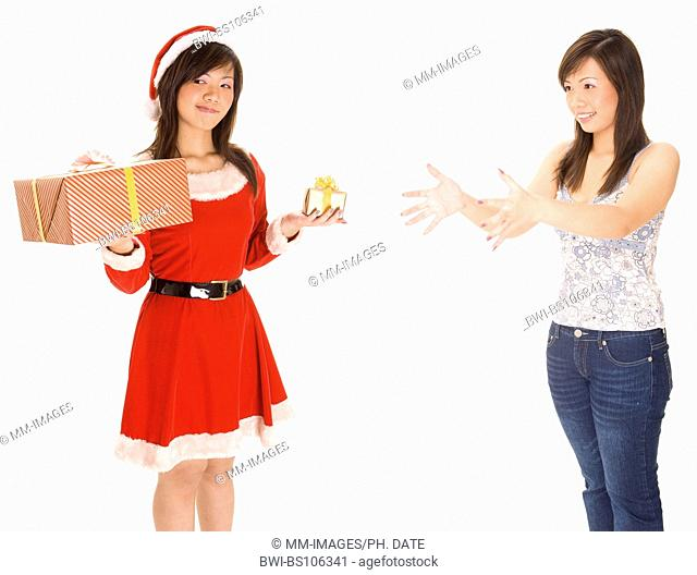 A female dressed as santa tries to decide whether to give the big or small present to the same woman dressed casually with arms outstretched