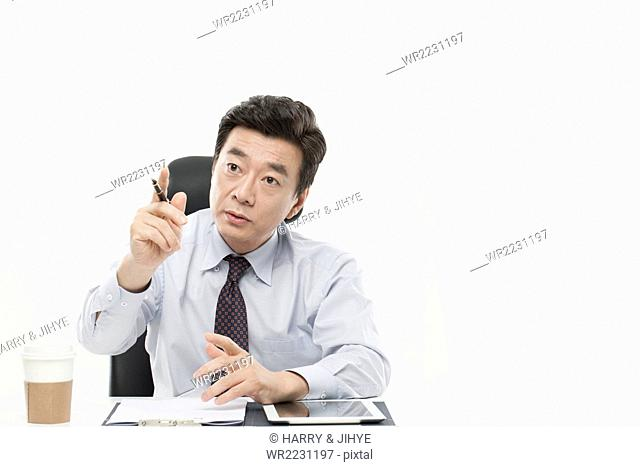 Senior man in business attire in serious face seated at desk and pointing with his finger with a pen in his hand