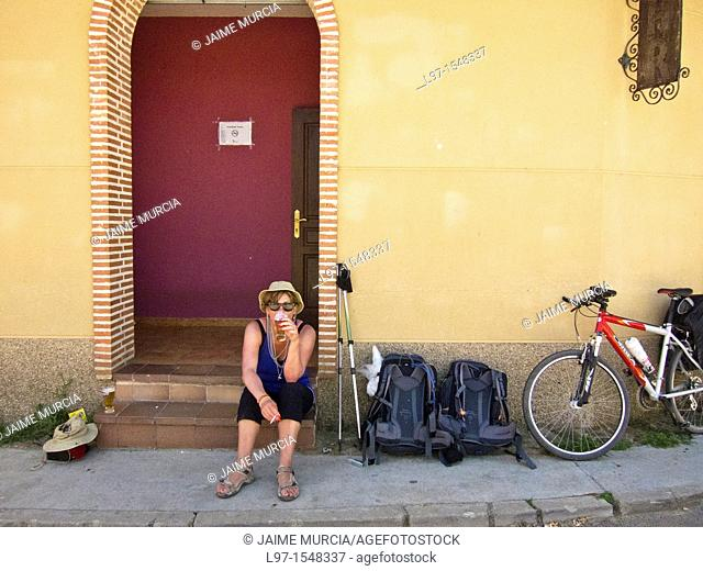 A women with a beer and cigarette outside of a bar along the Camino de Santiago, in the village of Ledigos