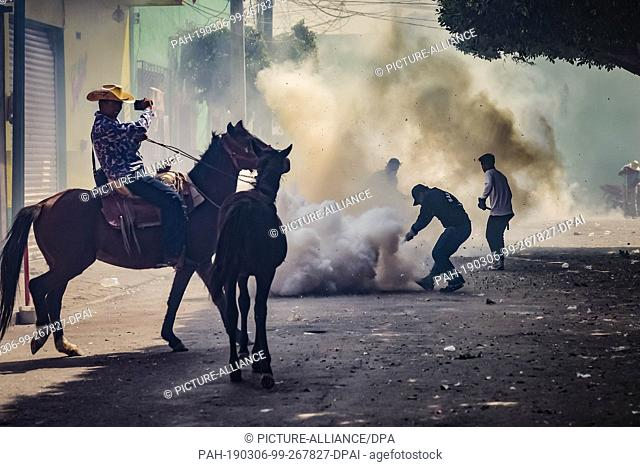 """05 March 2019, Mexico, San Juan de la Vega: A man on a horse laughs as he picks up participants of the """"""""Festival of Explosive Hammers"""""""" with his mobile phone"""