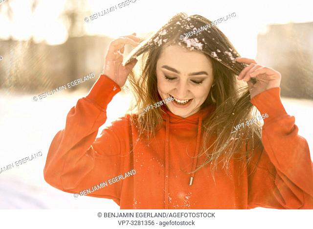 young woman with snow in hairs, winter season, wearing orange sweater, in Cottbus, Brandenburg, Germany
