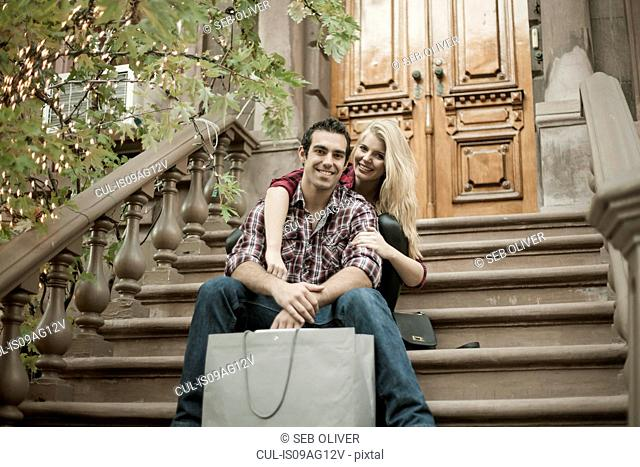 Young couple sitting on traditional city apartment steps
