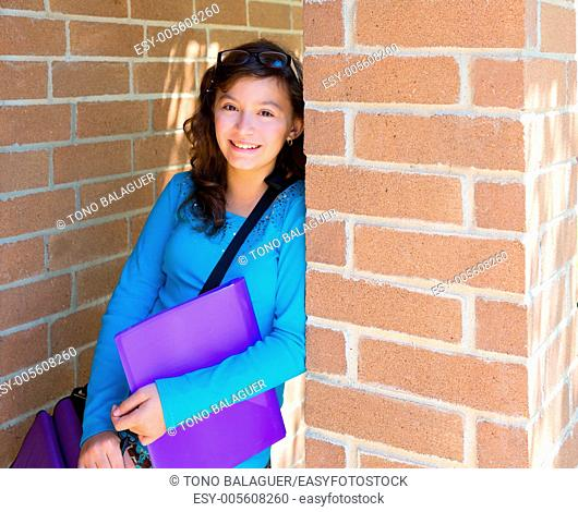 Schoolgirl teenager at school brick wall happy with folder and bag