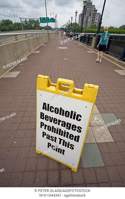 Entrance to a walking bridge with a sign prohibiting alcohol