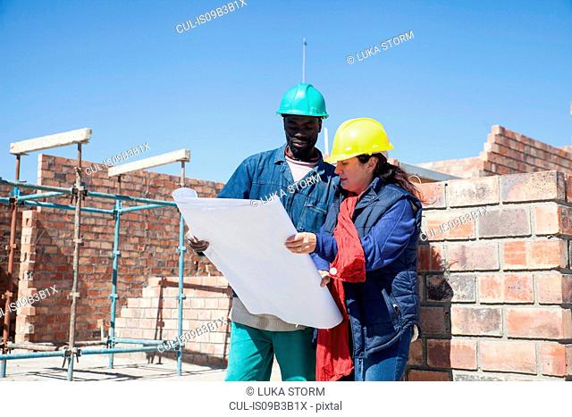 Site manager and builder looking at blueprint on construction site