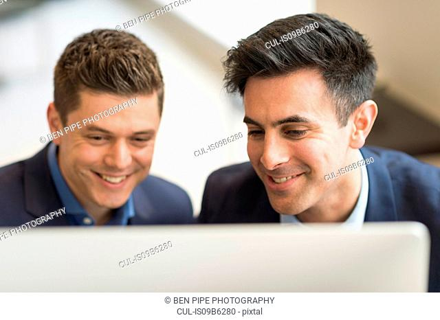 Two businessmen looking at computer in office