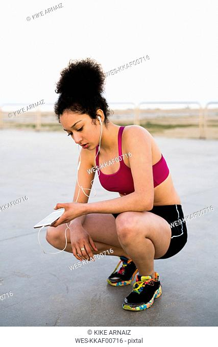 Young jogger with earphoes and cell phone