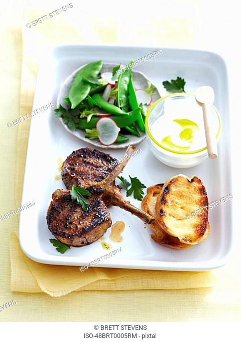 Plate of roasted lamb, bread and peas