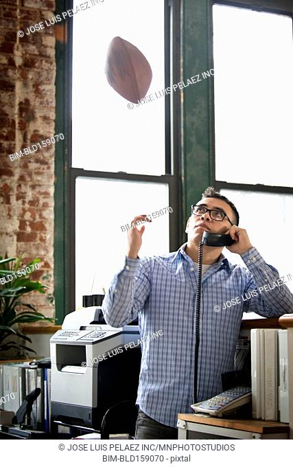 Hispanic businessman tossing football on telephone in office