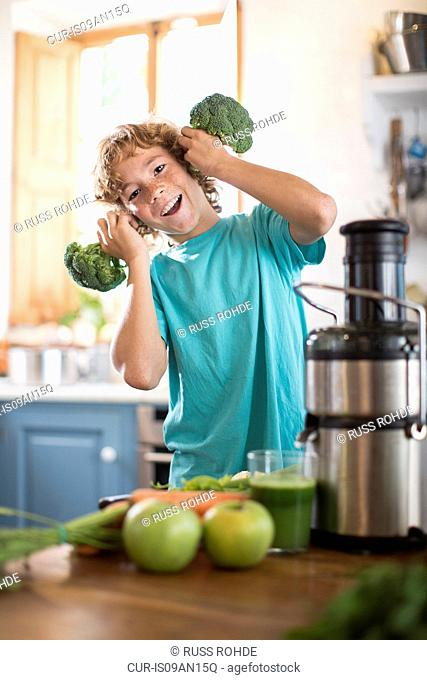 Teenage boy playing with broccoli in kitchen