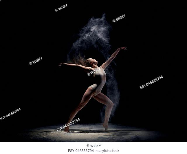 Young athletic woman dancing at dark studio in cloud of powder or dry paints