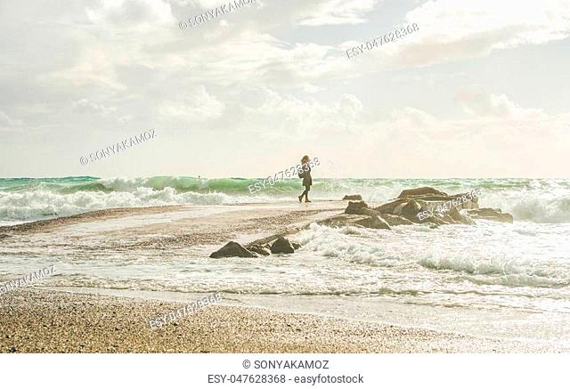 Young woman traveler standing on pier and looking at waves of stormy Mediterranean sea in winter, Alanya, Turlkey