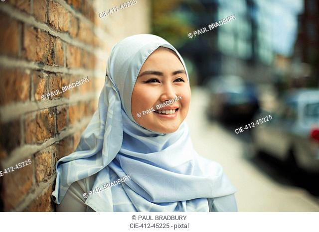 Portrait smiling, confident young woman in blue silk hijab