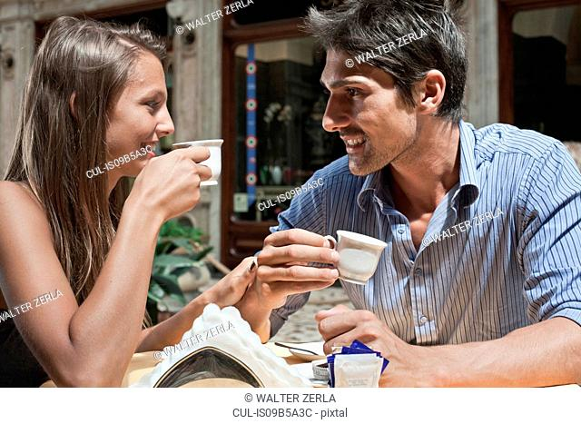 Young couple sitting outside cafe, drinking coffee, Turin, Piedmont, Italy