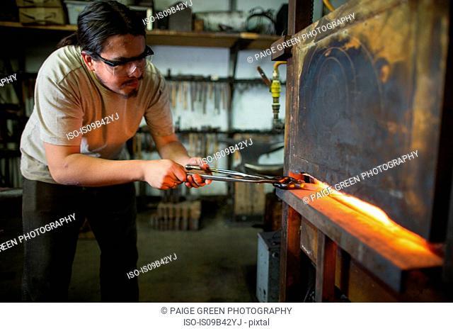 Male metalsmith removing metal workshop furnace