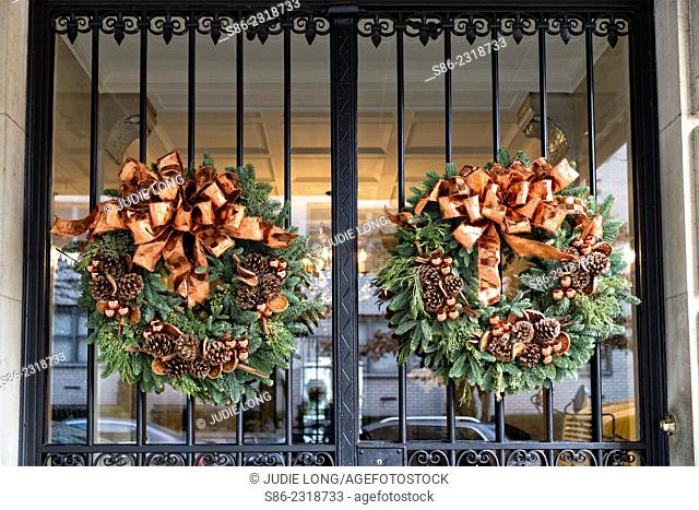 Christmas Wreaths with Pine Cones and Bows, Gracing the Wrought Iron Covered Glass Double Entry Doors of an Upscale Manhattan, New York City, Apartment Building
