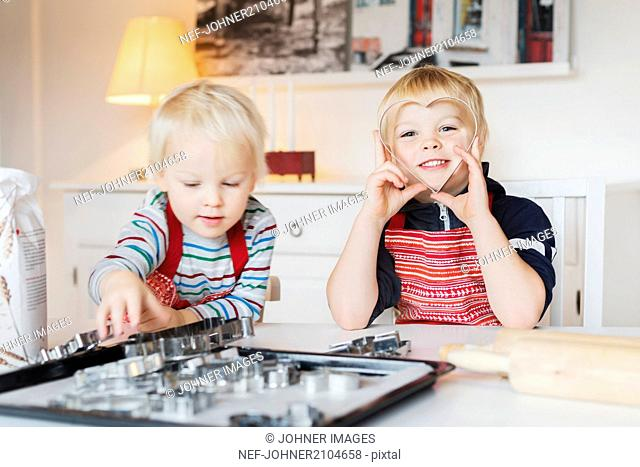 Two boys playing with cookie cutters at home