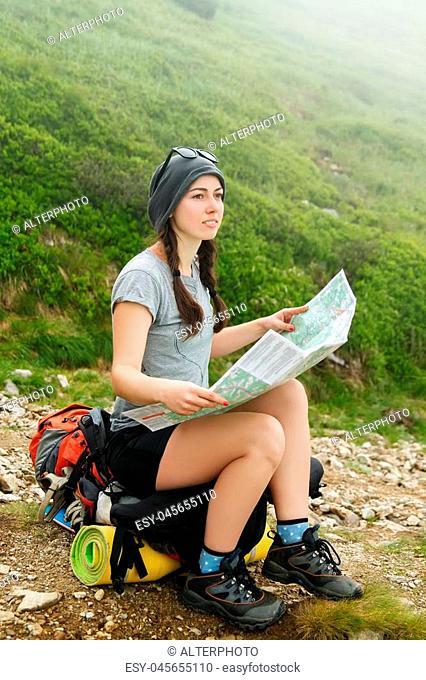 Girl tourist in mountain with fog read the map. Hiker watching the map. Girl tourist with map. Lifestyle concept active leisure tourism