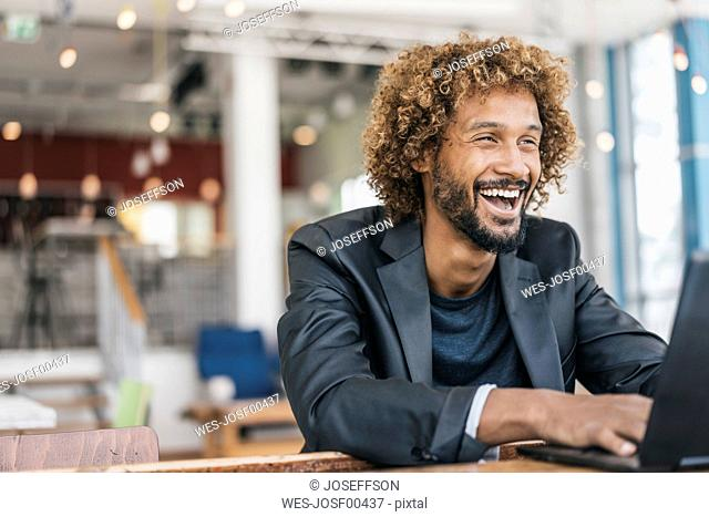 Successful young businessman using laptop