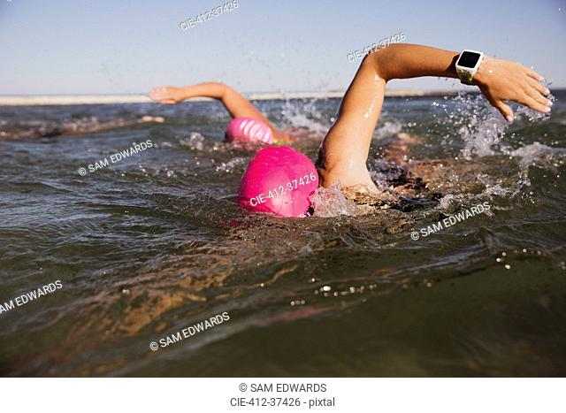 Female open water swimmer with smart watch swimming in sunny ocean