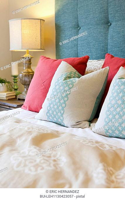 Patterned pillows arranged on bed in bedroom