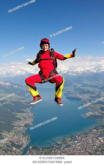 Woman skydiving over rural landscape
