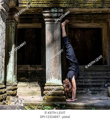 A woman does a hand stand at Ta Prohm Temple; Krong Siem Reap, Siem Reap Province, Cambodia