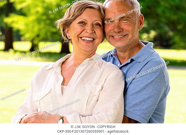 Senior citizen couple laughing at camera outdoors