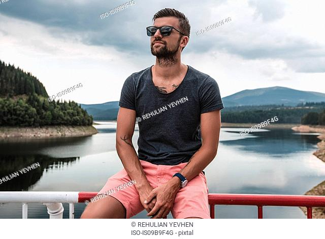 Man sitting on safety barrier by lake, Koralat, Zagrebacka, Croatia
