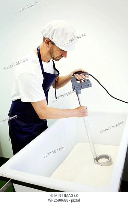 Man in a creamery, wearing apron and protective cap, stirring goats milk, making goats cheese