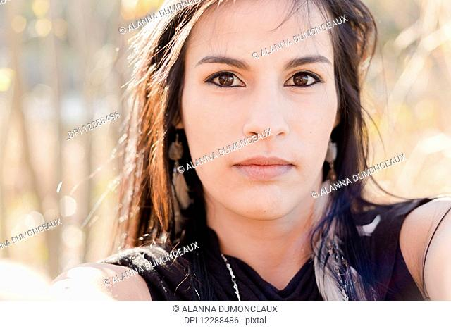 A young aboriginal female model looks at the camera in a concentrated stern gaze taking a selfie up close; Vancouver, British Columbia, Canada
