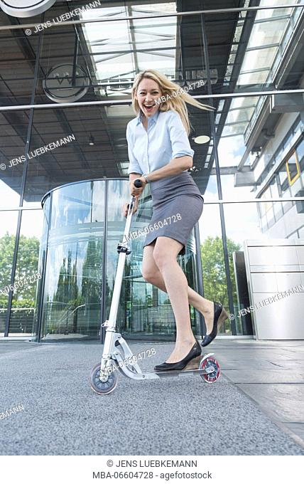 blond businesswoman drive laughingly a scooter