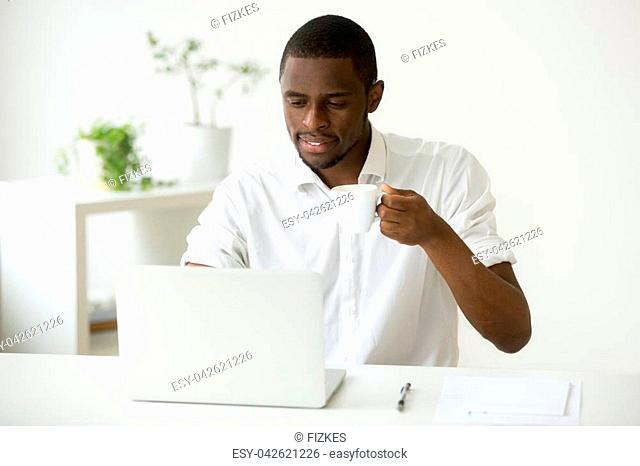 Smiling attractive african american man enjoying coffee while using laptop sitting at home office desk, black businessman checking online news or computer...