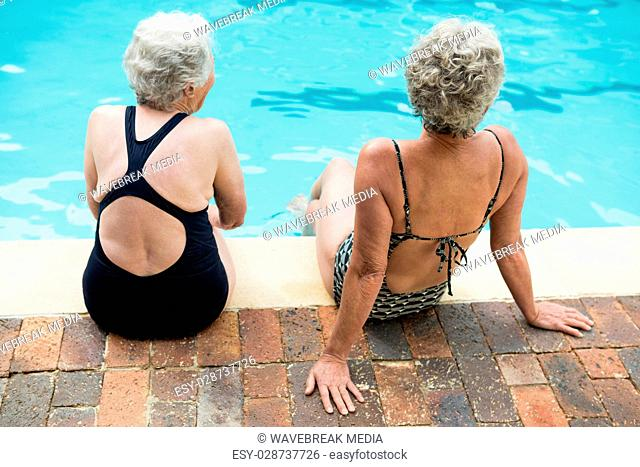 Two senior women sitting together at poolside
