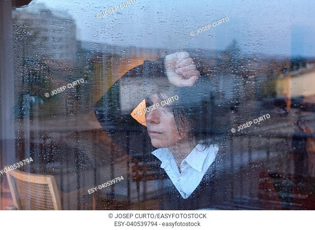 Woman looking out the window on a rainy day