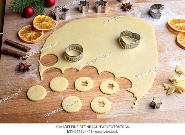 Cutting out shapes from rolled out dough to prepare traditional Linzer Christmas cookies