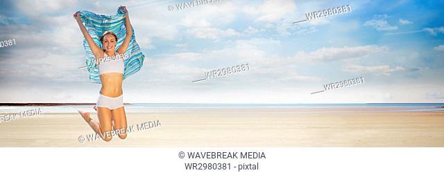 Woman in underwear with blanket celebrating on beach