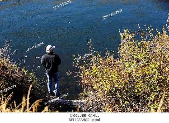 A man stands fishing on the shore of a lake; Oregon, United States of America