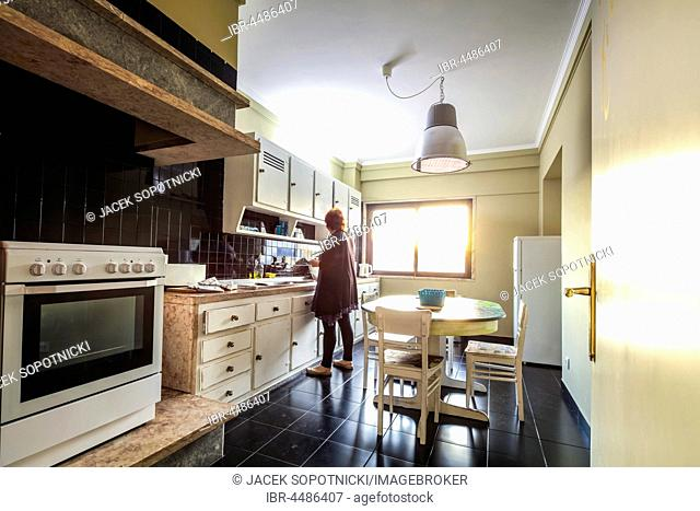 Woman standing in bright kitchen