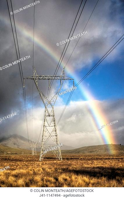 Power pylons, rainbow forms as evening sun lights up rain clouds, Mackenzie country, Canterbury, New Zealand