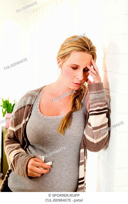 Unwell pregnant woman leaning against living room wall