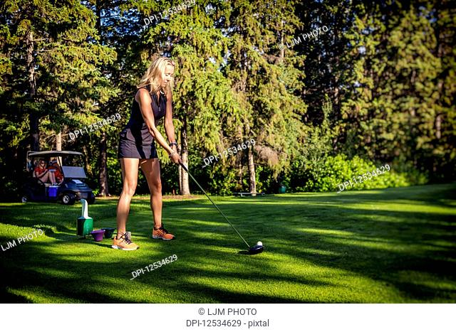 A digitally manipulated image of female golfer as she lines up her driver with the golf ball as two other golfers wait in the golf cart in the background;...