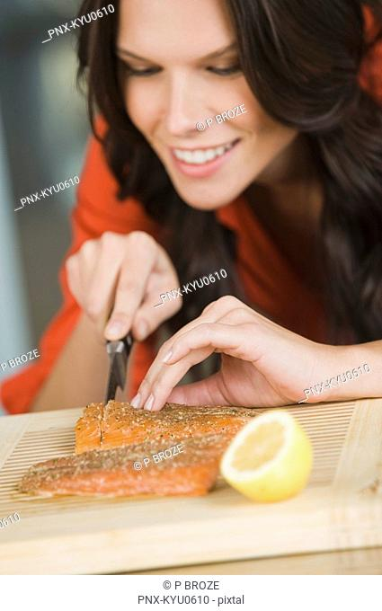 Woman cutting salmon slices