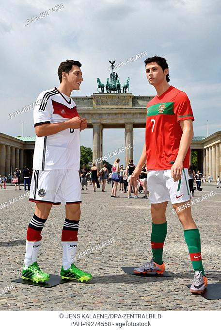 Wax figures of soccer player Mesut Oezil (L) and Cristiano Ronaldo of the Madame Tussauds wax museum are on display in front of the Brandenburg Gate in Berlin