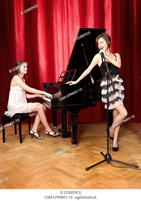 Duet with a young pianist behind a grand piano, looking at a beautiful lead singer